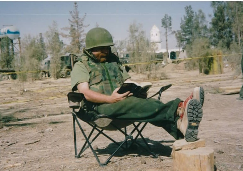 Me, pretending to read Pickwick Papers outside the media tent at Kandahar Airfield. The tin hat and flack jacket weren't exactly up to code but both were the price of admission for reporters to the base.