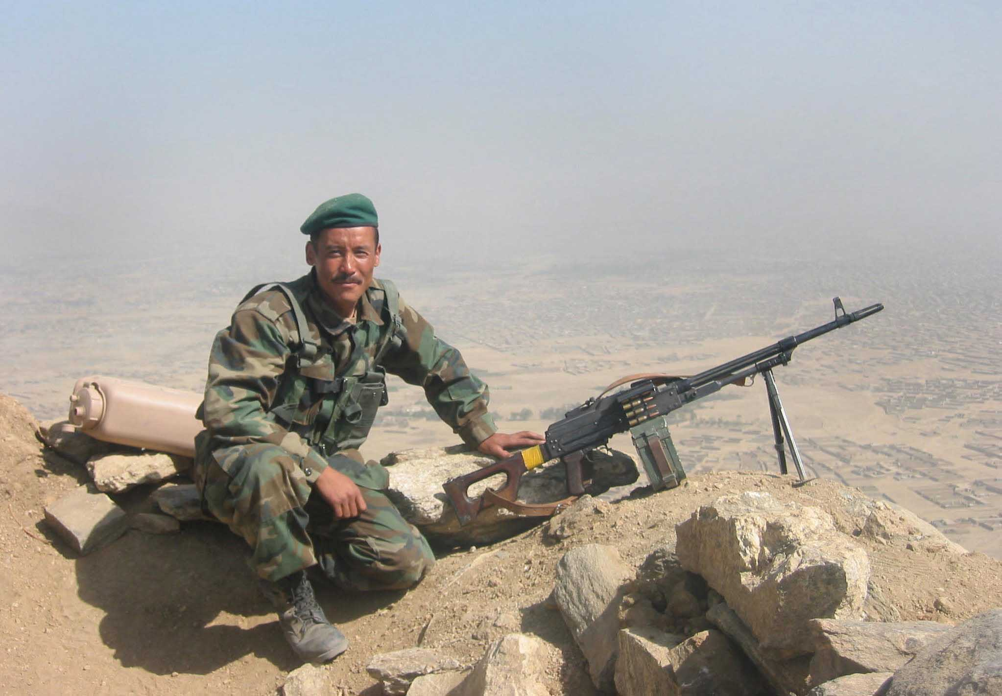 A soldier of the Afghan National Army poses next to his PKM machinegun at a hilltop observation post near Kabul