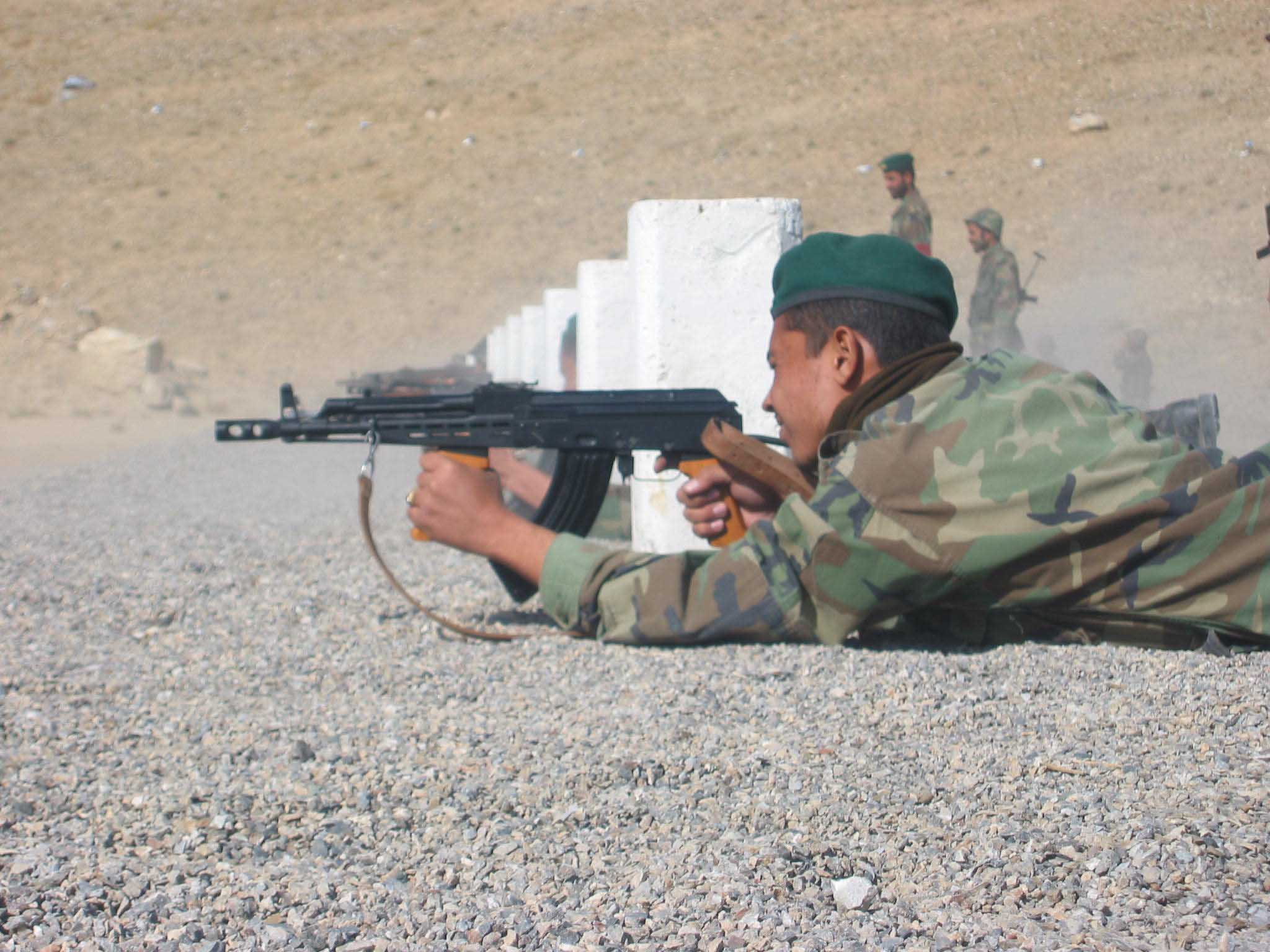 A young recruit to the Afghan National Army tries out his brand new Kalashnikov at a  training range near Kabul