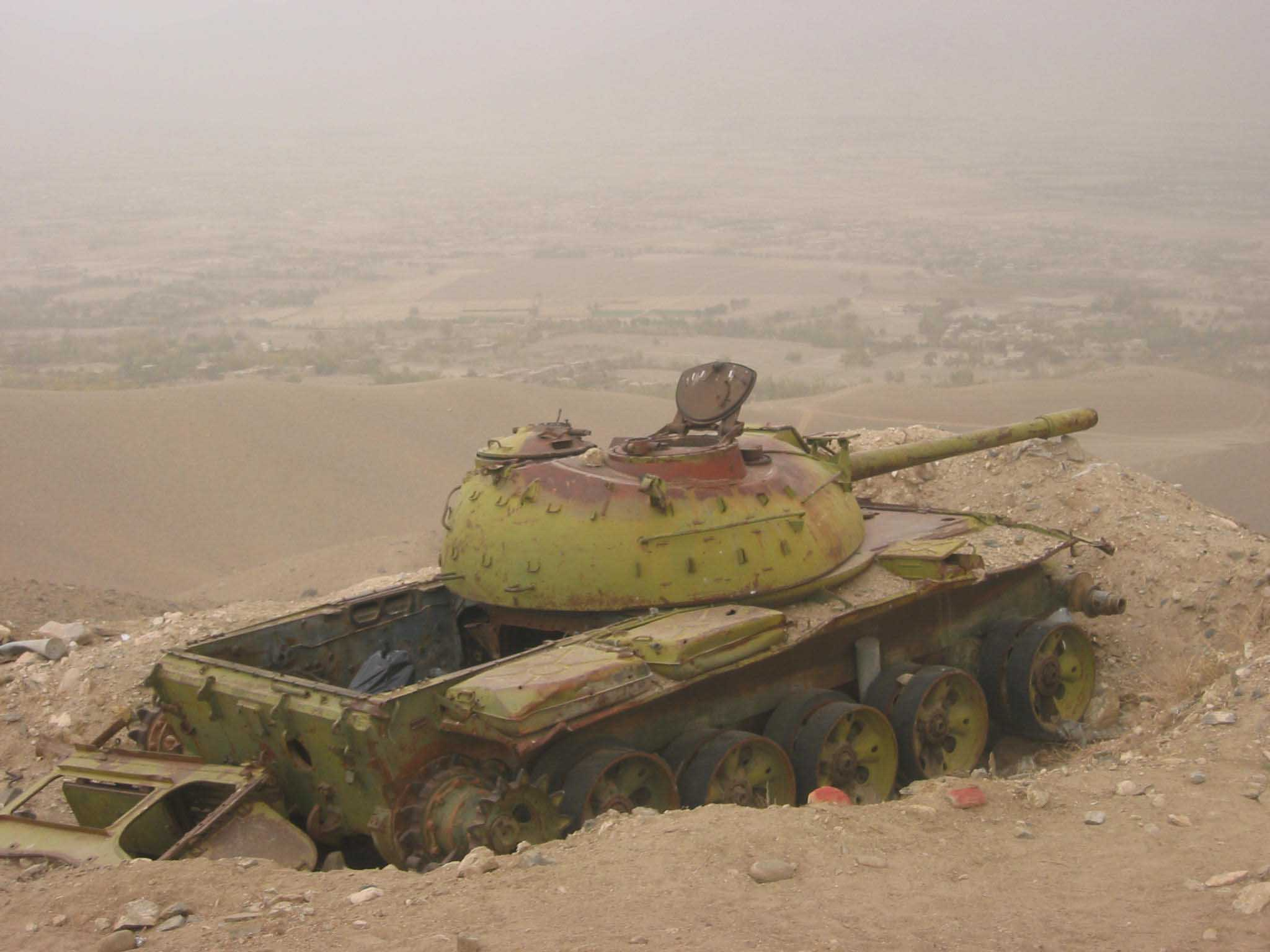 A derelict Soviet tank stands sentinel in a dug-in position in the mountains surrounding  Kabul in Afghanistan. The red rocks mark mines that have still not been cleared.